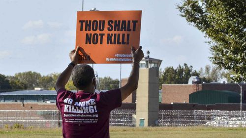 Protester Sylvester Edwards holds a sign up opposing the death penalty from across the street from the federal penitentiary in Terre Haute, Indiana.