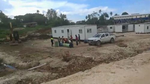 The footage shows one man digging a hole beside a concrete mixer, and construction workers studying a segment of pipe. (Ezuthullah Kalar)