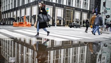 A pedestrian wearing a protective face mask is reflected in a rain puddle, Tuesday, March 17, 2020, in New York. New York state entered a new phase in the coronavirus pandemic this week.