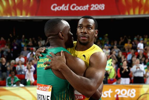 Simbine and Blake embrace after the shock upset. (Getty)