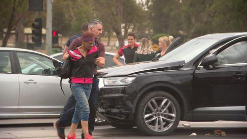 Police handcuff the female suspect at the crash scene.