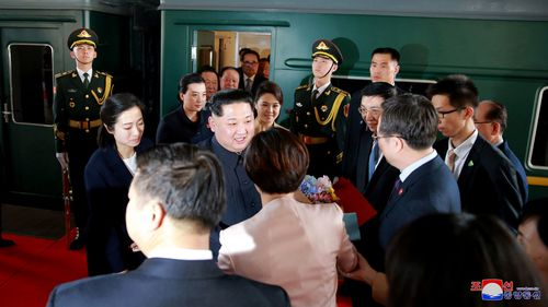 Kim Jong-un and wife Ri Sol Ju are greeted by President Xi Jinping and his wife on arrival. Picture: AP