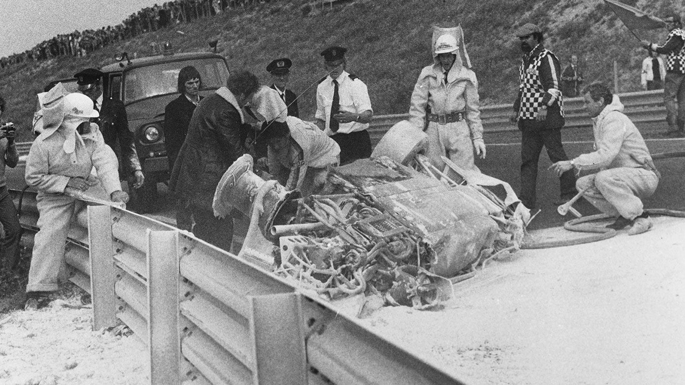 Marshals inspect Roger Williamson's upturned car during the 1973 Dutch Grand Prix.