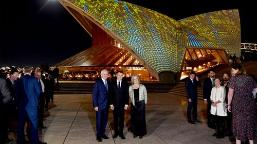 French President Emmanuel Macron (centre) poses with Prime Minister Malcolm Turnbull and his wife Lucy outside the Sydney Opera House. (AAP)
