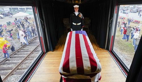 The flag-draped casket of George HW Bush passes through Texas on the special train, named 4141 after the 41st president.