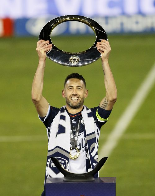 Carl Valeri of the Victory holds the trophy. (AAP)