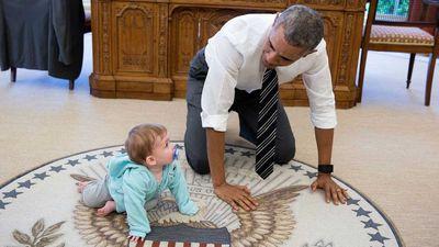 Obama crawls on the ground alongside White House Communications Director Jen Psaki's daughter Vivi.