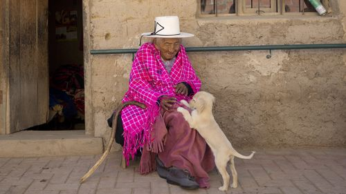 """In this Aug. 23, 2018 photo, 117-year-old Julia Flores Colque plays with """"Chiquita,"""" one of the family pet dogs"""