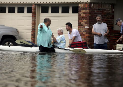 People walk out of their flooded Meyerland streets in Houston. (AP)