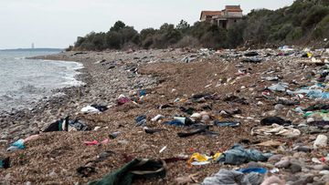 A beach near Ayvacik on the Turkish coast is strewn with rubble after a boat smuggling migrants to Greece slammed into rocks offshore. (AAP)