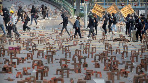 Protesters walk past barricades of bricks on a road near the Hong Kong Polytechnic University in Hong Kong.