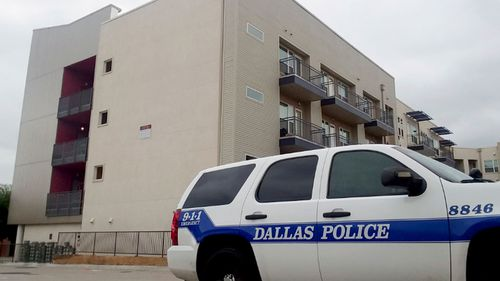 A Dallas Police vehicle is parked near the South Side Flats apartments where the shooting took place.