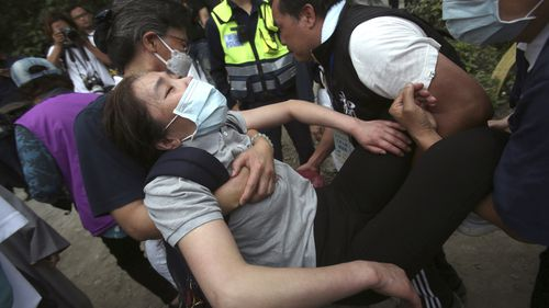 A distressed woman is carried away as families mourn for the victims in a train accident near Taroko Gorge in Hualien, Taiwan