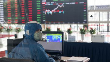A worker wearing a protective suit reacts in front of an infrared temperature machine in the lobby of the Shanghai Stock Exchange building in Shanghai.