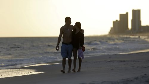 In this March 12, 2020 photo, people walk on the beach in Gulf Shores, Ala. The spring of coronavirus feels a lot like the summer of oil to residents along the Gulf Coast. Bars and restaurants are empty in Florida because of an invisible threat nearly a decade after the BP oil spill ravaged the region from the ocean floor up.