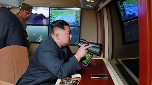 North Korean leader Kim Jong Un, equipped with binoculars, supervises a rocket launch test.