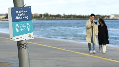 People walk along St Kilda Beach to get their daily exercise.