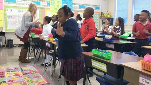 A US teacher has been praised after a video was posted online showing her leading her class in a pre-lesson dance routine. (Facebook/St. John Catholic School)
