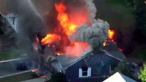 In this image take from video provided by WCVB in Boston, flames consume a home.