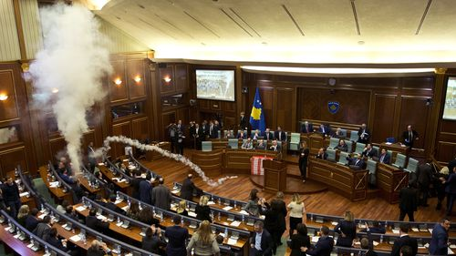 The Kosovo parliament was halted yesterday during a vote on a proposed border demarcation law after the opposition used tear gas. Picture: AAP.