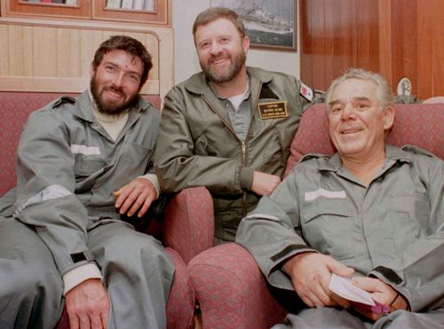Raydon Gates, centre, with Thierry Dubois, left, and Tony Bullimore in the captain's cabin aboard HMAS Adelaide in 1997. (Photo: AAP).