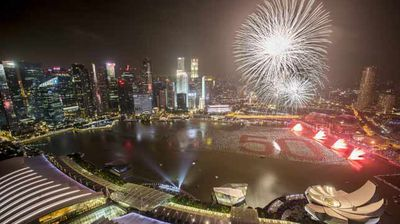Fireworks go off above an arrangement of 5000 red balloons spelling the number '50' on the Marina Bay in Singapore. (AAP)