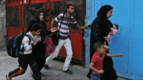 Palestinians run for shelter as they hear bombing in the distance while they flee their homes in the Shajaiyeh neighborhood of Gaza City, after Israel had airdropped leaflets warning people to leave the area, Wednesday, July 16, 2014. (AAP)