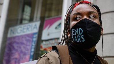 "A woman wearing an ""END SARS"" protective face mask speaks with the police outside the Nigerian Consulate during a demonstration on October 21, 2020 in London."