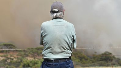 Local farmer John Stanton looks on as bushfires sweep through Stokes Bay on Kangaroo Island, southwest of Adelaide, Thursday, January 9, 2020. A convoy of Army vehicles, transporting up to 100 Army Reservists and self-sustainment supplies, are on Kangaroo Island as part of Operation Bushfire Assist at the request of the South Australian Government. (AAP Image/David Mariuz)