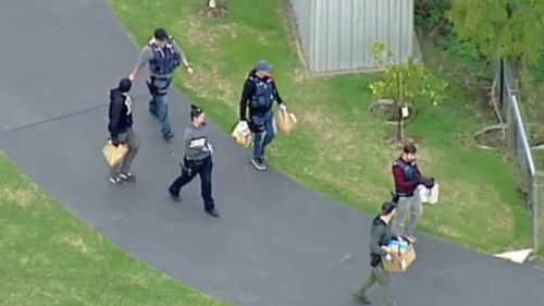 Officers were shown carrying several brown paper bags from the scene. (9NEWS)