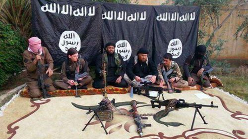Bilardi poses with other fighters infront of an ISIL flag.