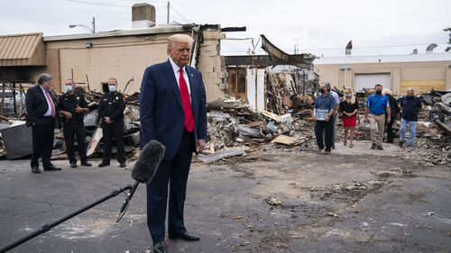 Donald Trump stands in front of the ruins of burned-out stores in Kenosha, Wisconsin.