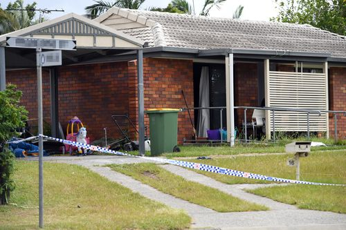 Children's play toys remain in the front yard of an Eagleby home where the bodies of two people were found yesterday (AAP).