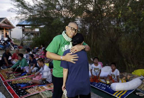 An Indonesian man hugs his daughter who survived the earthquakes and tsunami as they reunite at an open air camp in Palu.
