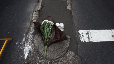 A single bunch of flowers and two cups of coffee are left as a sign of respect. (Getty)