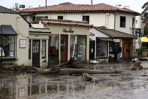 Debris and mud cover the street in front of local area shops after heavy rain brought flash flooding on Tuesday. (AAP)