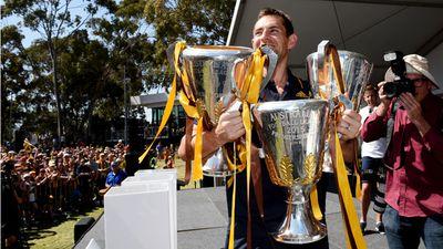 Skipper Luke Hodge with the 2013-2015 premiership cups. (AAP)