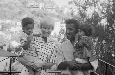 Sammy Davis, Jr., and his wife, actress May Britt, pose with their adopted son Mark Sidney Davis (left). Sammy holds their 16-month-old daughter, Tracey.