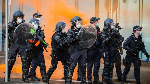 Police have bottles and flares thrown towards them during a protest at the CFMEU headquarters in Melbourne,  on Monday.