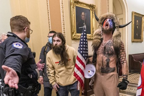 In this Wednesday, January 6, 2021 file photo, supporters of President Donald Trump, including Jacob Chansley,  with fur hat, are confronted by Capitol Police officers outside the Senate Chamber.