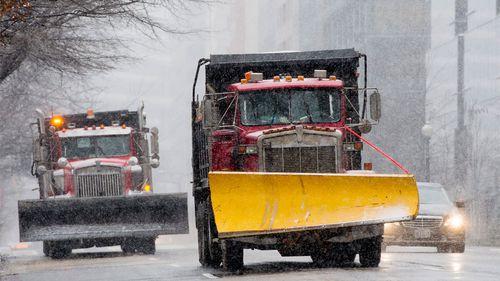 Snow plows drive down the street as the blizzard Jonas begins in Washington, DC. (AAP)