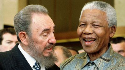 In this May 19, 1998  photo, Cuban leader Fidel Castro, left, shares a laugh with South Africa President Nelson Mandela at a meeting of the World Trade Organization in Geneva, Switzerland. (AAP)