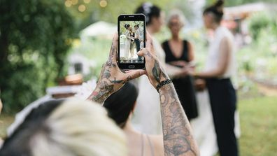 Guest taking wedding photo on phone