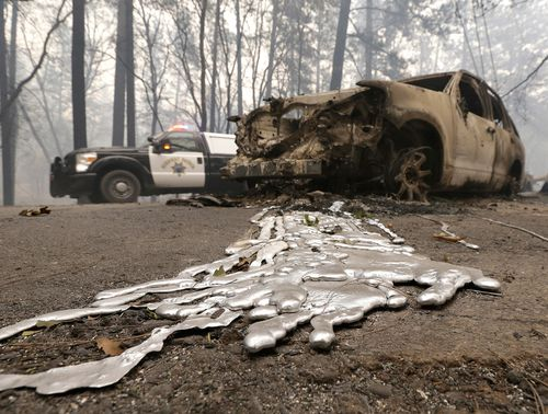 A California Highway Patrol vehicle passes a destroyed vehicle.