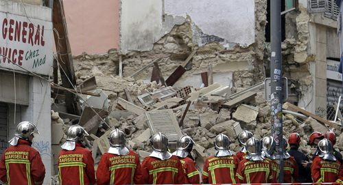 Firefighters work at the scene where buildings collapsed in Marseille.