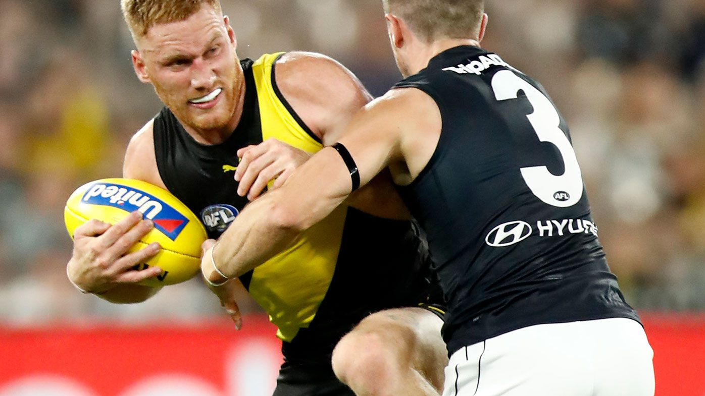 Nick Vlastuin of the Tigers is tackled by Marc Murphy of the Blues during the round one AFL match between the Richmond Tigers and the Carlton Blues.