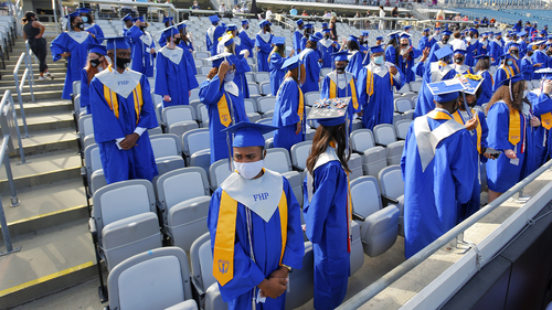 Graduates of the Frank H. Peterson Academies of Technology stand as classmates file in to their socially distanced seats at the start of Friday morning's graduation ceremony in TIAA Bank Field.