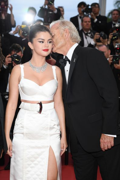 Bill Murray whispers into Selena Gomez's ear.