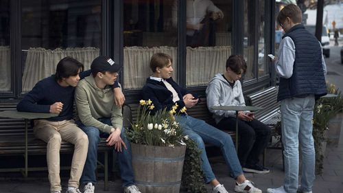 Young people hang out in front of a restaurant in Stockholm, Sweden. Social distancing is recommended but not applied in the country.