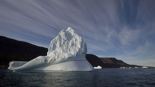 In this July 21, 2011, file photo, an iceberg floats in the sea near Qeqertarsuaq, Disko Island, Greenland.  (AAP)